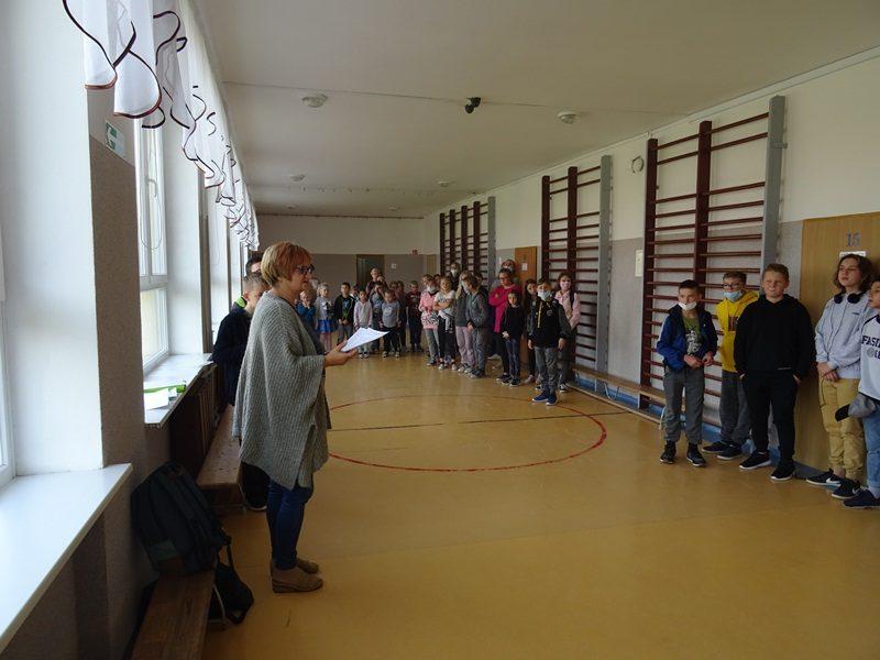 Korytarz szkolny. Nauczyciela stoi przy oknie i informuje uczniów o wynikach konkursu. Uczniowie stoją po drugiej stronie, przy ścianie.